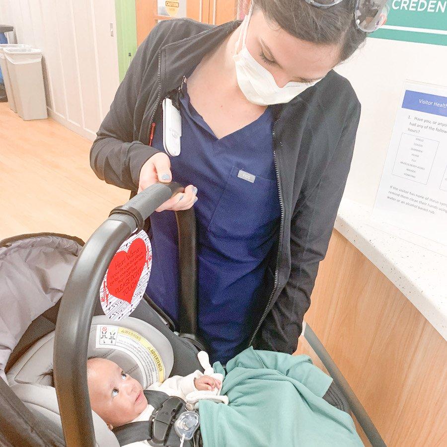 NICU nurse holding baby in car seat